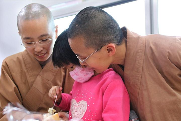 法師親切的教導孩子準備齋僧物
